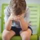 Besisūpuojantis ant kėdės berniukas susiėmęs už galvos